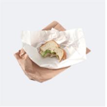 Mordida de sandwich sobrante en una envoltura de papel en una bolsa de papel