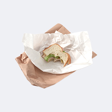 Leftover sandwich bite on paper wrapper on paper bag